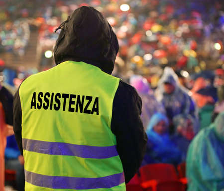 boy with high visibility jacket and  text ASSISTENZA that means Assistance in Italian language and many people before the live event and it is raining