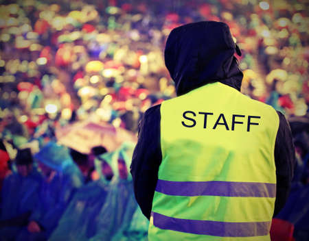 boy of Staff with high visibility jacket during live outdoor concert when it is raining with old toned effect