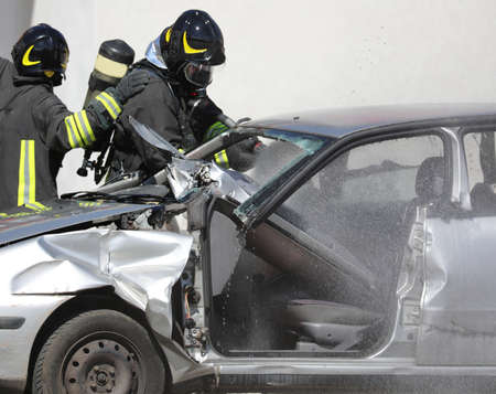 Team of firefighters during fire fighting of a destroyed car after a serious car accident