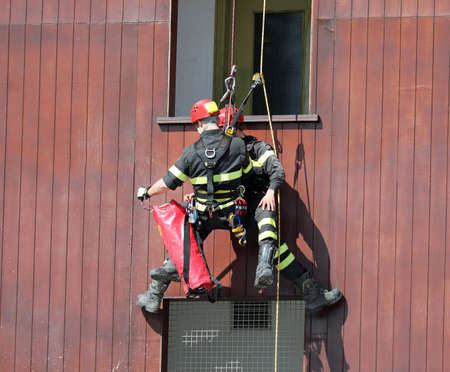 rescue exercises with abseiling by a firefighter and a person who simulates the injured person