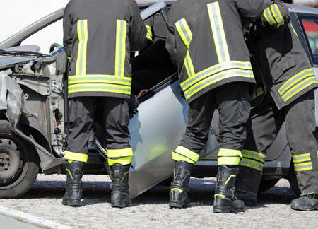 firemen remove the door of a destroyed car after a serious car accident to recover the injured motorist