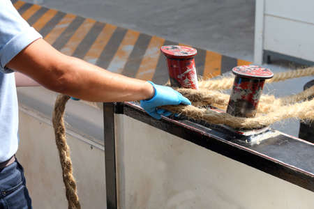 sailor ties a hemp rope to the dock to facilitate the mooring of a boat
