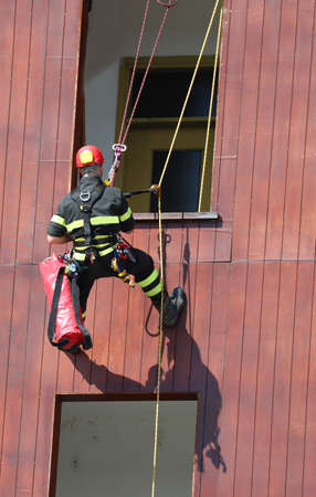 brave climber of the fire brigade during an exercise to access the house from the window lowering himself from above with a safety rope