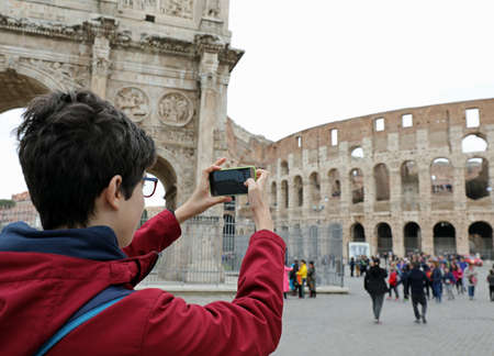 Young boy with glasses takes picture of Colosseum with his smart phone in Rome Italy Imagens