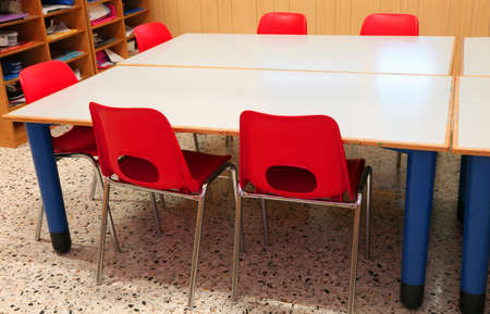 small red chairs in the classroom of a kindergarten without children Фото со стока