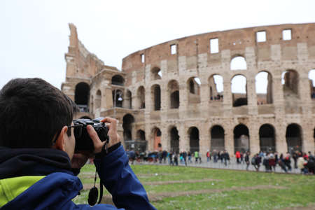young photographer taking a picture of the famous Roman Colosseum amphitheater in winter in Rome in Italy