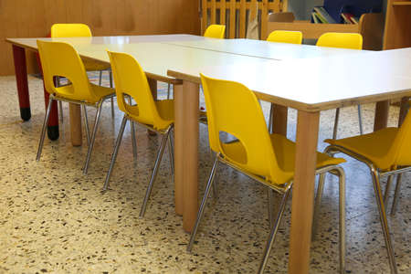 small yellow chairs and low tables inside a school classroom of the school without the kids Foto de archivo - 124656208