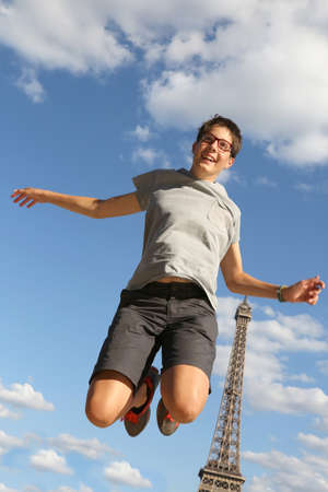 Happy boy jumps with Eiffel Tower in background in Paris France