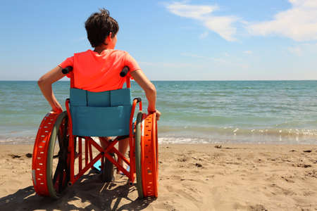 beach and a young boy on the wheelchair by the sea in summer Фото со стока