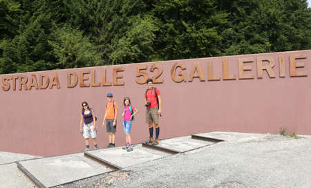 Family of 4 person in Italy in Pasubio Mountain. The text means Road of 52 Tunnel in italian Language Фото со стока