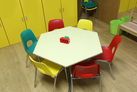 low chairs and hexagonal table of a kindergarten class without children Фото со стока