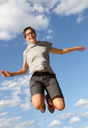 Very happy boy jumps on blue sky Фото со стока