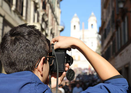 young photographer with digital camera in Via dei Condotti in Rome Italy and the church of the Trinity in the background Фото со стока