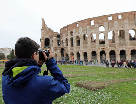 young journalist with his digital camera takes photos of Colosseum in Rome Italy