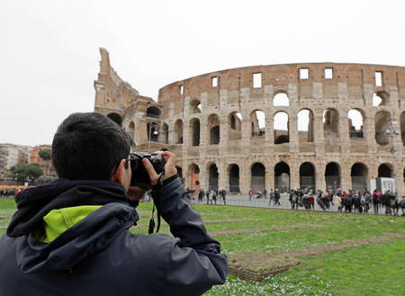young boy takes photos of Colosseum in Rome Italy in winter