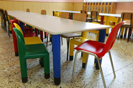 interior of the refectory with small tables and colored chairs in the nursery school without children Фото со стока