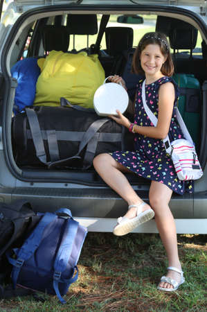 smiling girl loads her purse in the trunk of the car before leaving for the holidays