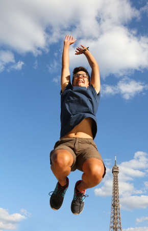 Young boy jumps with Eiffel Tower on background in Paris France
