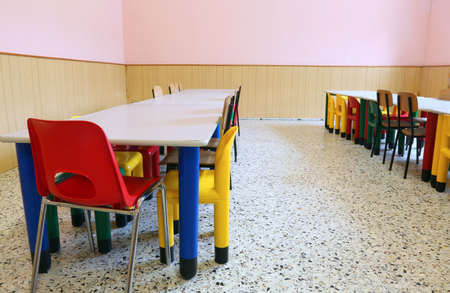 small chairs and long tables of a refectory of the nursery school without the kids