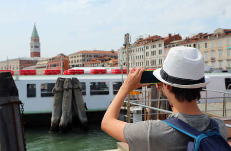 young boy takes picutres with his smart phone in Venice Italy Фото со стока