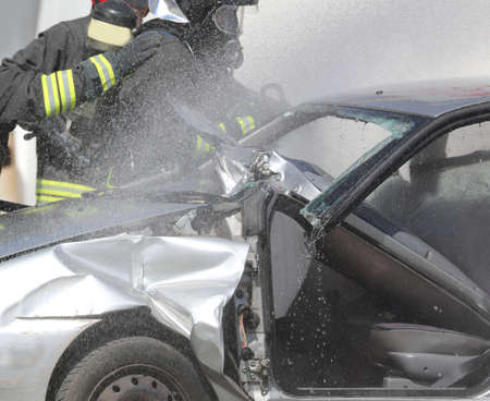 fire brigade team during the fire extinguishing of a destroyed car after the road accident