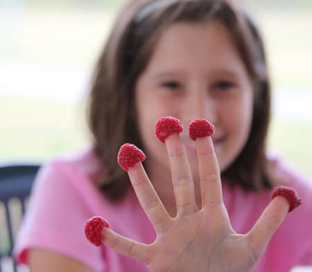 little girl with five raspberries on the hand