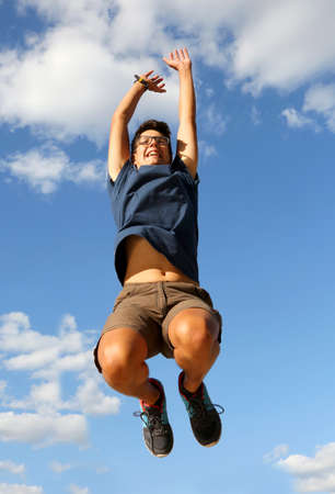 young boy jumps on blue sky with clouds