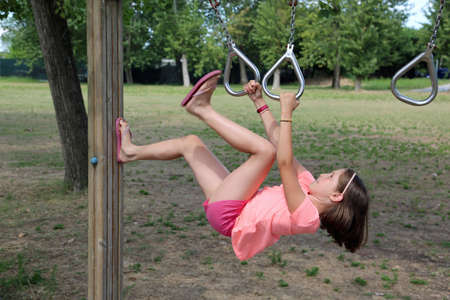 little girl does a gymnastic exercise with rings in a health path