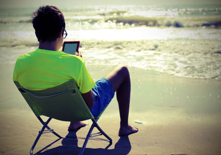 young boy reads an e-book on seashore in summer  with old toned effect