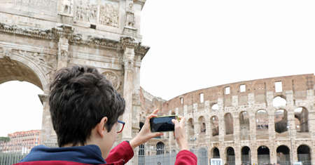 boy photographs the Colosseum in Rome with a mobile phone
