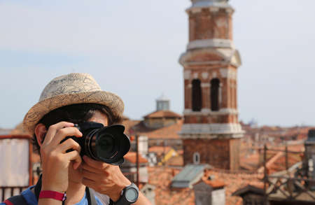 young boy with hat takes picutres with his digital camera in Venice Italy