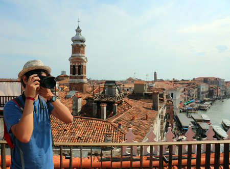 boy with a straw hat photographs the panorama of Venice from above Фото со стока
