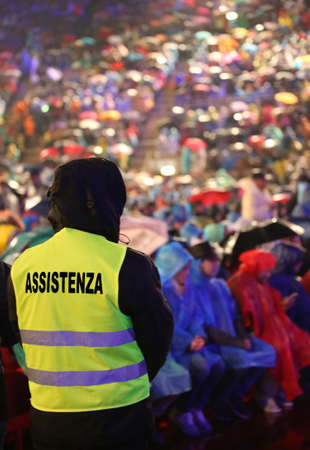many people during a live concert and a boy with jacket with text ASSISTENZA that means Assistance in Italian language