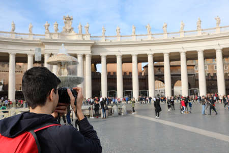 young photographer in St. Peters Square in the Vatican while he is photographing the great colonnade of the architect Bellini
