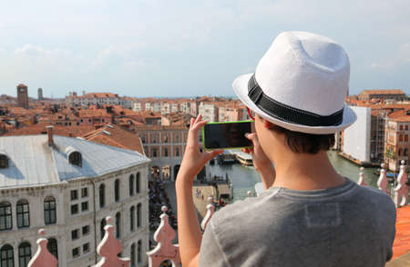 young boy with white hat takes picutres with smartphone in Venice Italy Фото со стока