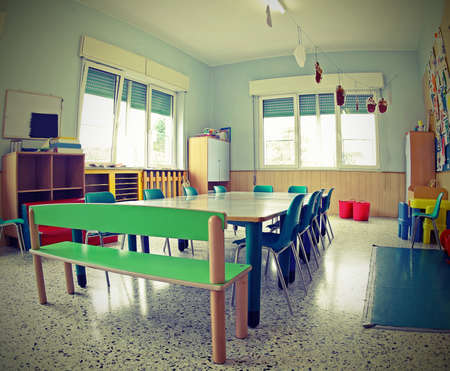small chairs and low tables inside a school classroom without children with vintage toned effect Foto de archivo - 124656504