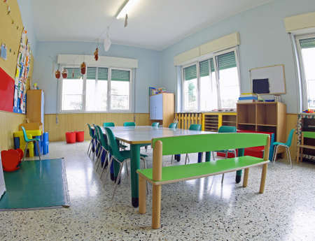 small green chairs and low tables inside a school classroom of the school without the kids Foto de archivo - 124656507