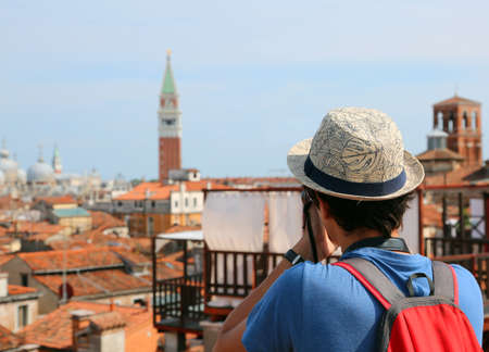 boy with a straw hat photographs the bell tower of the Basilica of San Marco in Venice from the Fondaco dei Tedeschi Фото со стока