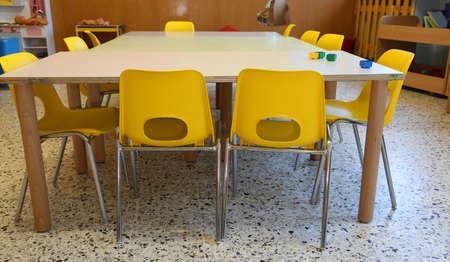 small yellow chairs in the classroom of a school without children