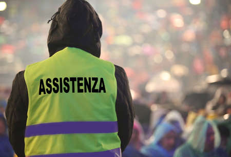 boy with yellow high visibility jacket and the text that means ASSISTANCE in Italian language and it is raining Imagens