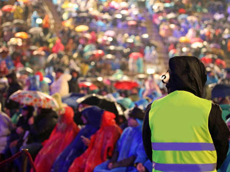 man with yellow jacket during live event and many people when piss down