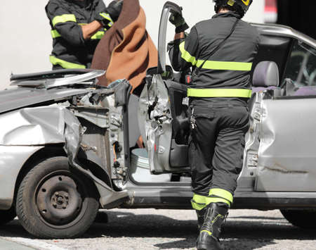broken car after road accident and the firemen in action Stok Fotoğraf