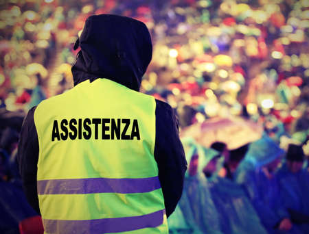 boy with high visibility jacket and  text ASSISTENZA that means Assistance in Italian language and many people before the live event