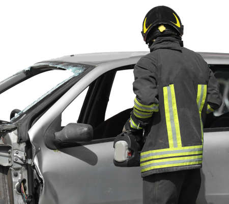 firefighter in uniform with helmet and a broken car after the road accident