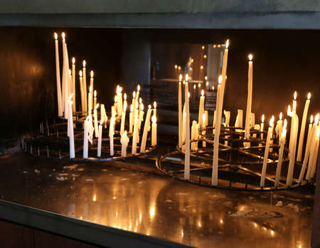 many votive candles lit by the faithful in church as religious supplication