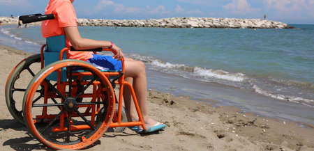boy in a wheelchair admires the sea from the shore