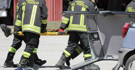 Rome, RM, Italy - May 16, 2019: firemen stretcher bearer and a wounded person after road accident Редакционное