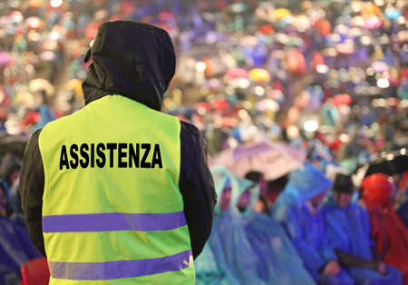 boy with high visibility jacket and refractive inserts for low light condiction with text ASSISTENZA that means Assistance in Italian language during the live concert