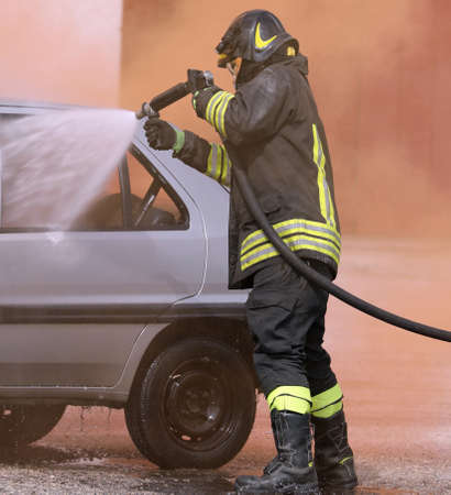 brave Firefighter with helmet uses foam during a road accident on the broken car Banco de Imagens