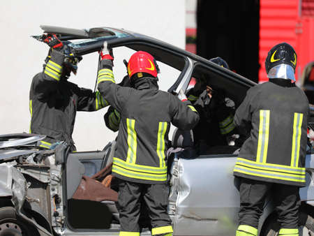 broken car after road accident and the firemen team in action